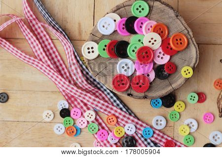 Colorful plastic buttons for sewing on wood background