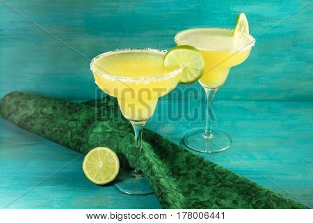 Lemon Margarita cocktails with wedges of lime on a vibrant turquoise background with copy space. Selective focus