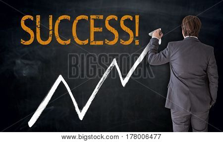 Businessman writes success on blackboard concept picture