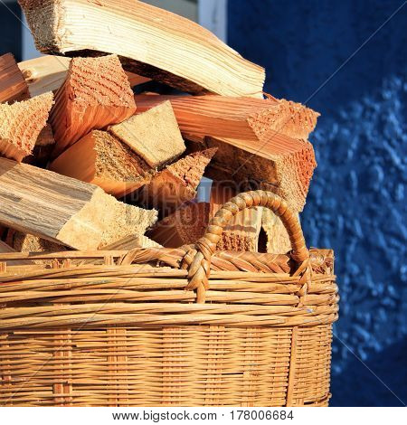 sunny landscape, basket with chopped firewood in the basket at the table - alternative energy