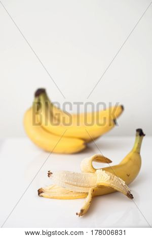 A Bunch Of Bananas And One Peeled Banana On White