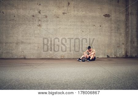 Tired Athlete Resting Next To Kettlebell