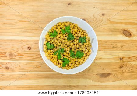 Bowl of chickpeas and parsley on wood table. Raw gram chickling and leaves of parsley from top view in a deep plate