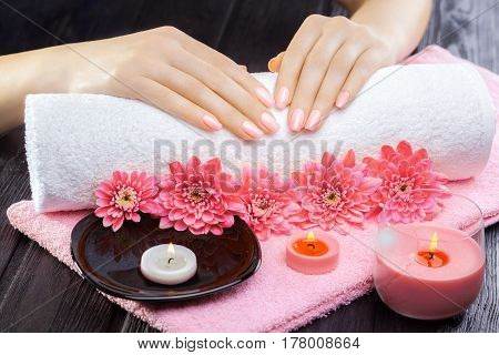 beautiful pink manicure with oil and candles, chrysanthemum and towel on the black wooden table. spa