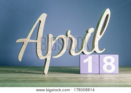 April 18st. Day 18 of month, daily calendar on wooden table with purple or violet background. Spring time theme.