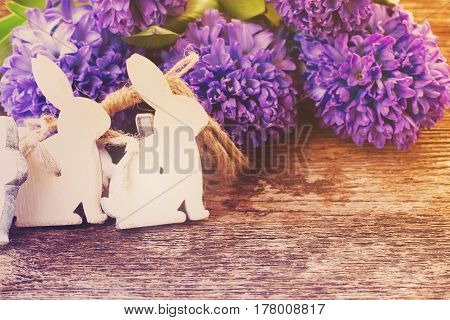 withe easter rabbits and hyacinth flowers on table, retro toned
