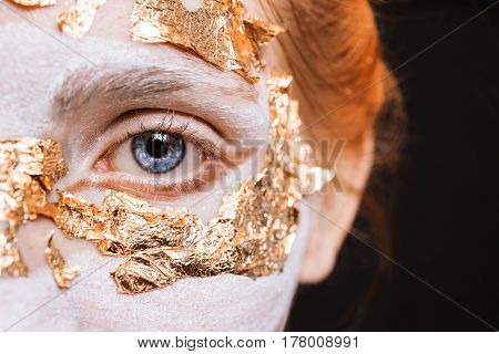 Blue eye closeup. A girl with an unusual make-up with gold leaf. Anonym. Masquerade Halloween. An open eye. A beautiful blue eye. Looking through the eyes of the camera