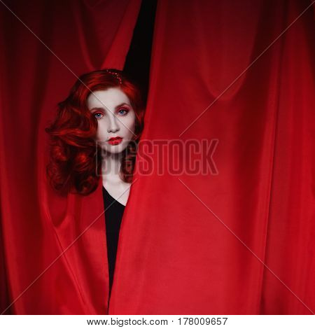 A woman actress with red curly hair in a black dress looking out of a red fabric. Red-haired actress with pale skin a thin waist blue eyes a bright unusual appearance red lips. Retro makeup. Theatre actress. Woman actress