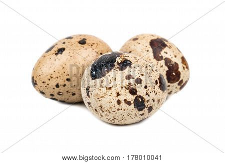 Three raw quail eggs on a white background