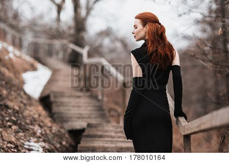 Beautiful lady. Striking lady girl with long red hair in black clothes. Woman lady in black dress and fur around neck with long black gloves posing on background of winter nature. Female lady street style. Beautiful elegant model