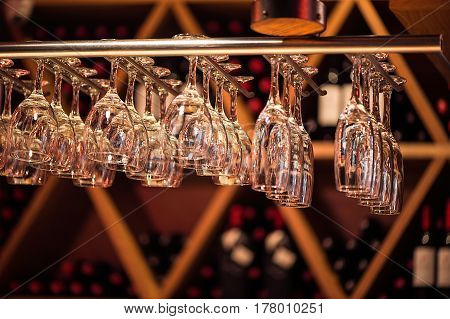 Glasses champagne hangs above the bar counter in the bar. Glasses cocktail hanging glasses over a bar rack.