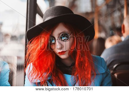 Woman with red curly hair in a blue coat and black round glasses riding on the bus. Red-haired girl in bus with pale skin and bright appearance with black hat on head and looking out the window. Street style. Ride in a bus