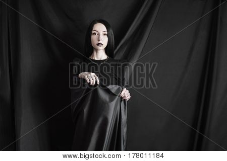 Emotional portrait of seductive brunette girl with long straight black hair with a natural make-up on a black background. Seductive woman in black dress wrapped in black cloth. Femme fatale witch. Seductive model. Seductive girl