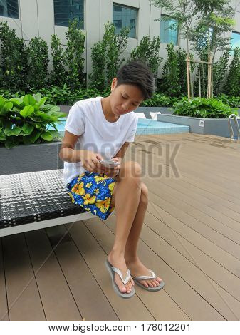 Young Filipino woman sitting poolside holding a mobile phone