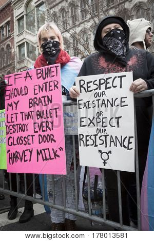 45th Presidential Inauguration, Donald Trump: Reference to Harvey Milk and Respect Our Existence Or Expect Our Resistance on protestors signs near the security checkpoint, WASHINGTON DC - JAN 20 2017