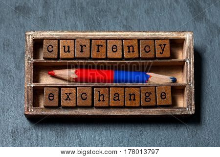 Currency exchange concept. Vintage box, wooden cubes phrase with old style letters, red blue pencil. Gray stone textured background. Close-up, up view, soft focus