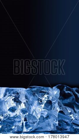 Piece of ice on blue background. Macro view transparent glacial crystal gems objects. Frozen water abstract shapes, soft focus. copy space.