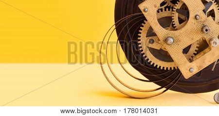 Vintage mechanic clockwork mechanism, spring bronze cogs wheels macro view. Shallow depth of field, selective focus. Yellow colorful background. Copy space.