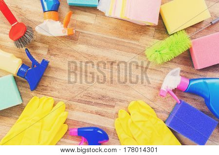 Spring cleaning concept - colorful sprays botles and rubbers frame, retro toned