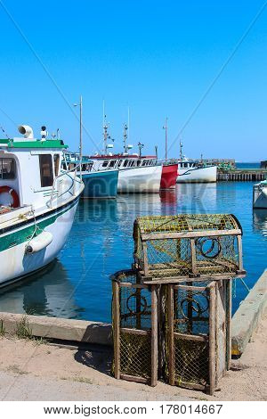 Fishing boats at a port in Magdalen Island with lobster traps in the foreground