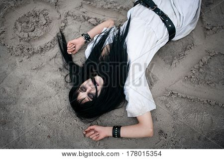 Crazy Young Woman Lying On Sand With Painted Symbols And Looking