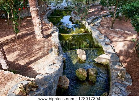 Beautiful small waterfall with cascades in Reina Sofia Park, Guardamar del Segura. Valencia, Spain