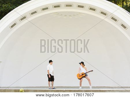 Relationship goals concept. Couple on romantic date. Woman playing guitar man jumping next to her