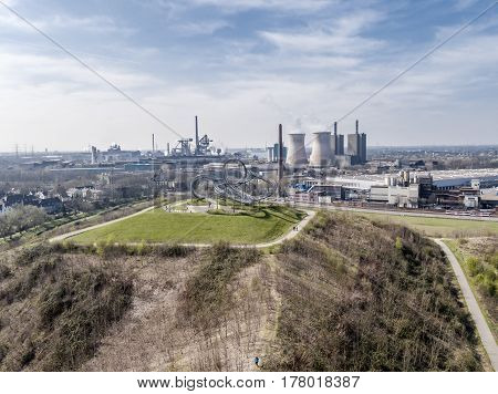 DUISBURG / GERMANY - MARCH 24 2017 : Landmark Tiger and Turtle standing on a hill while HKM is producing steel in the background aerial