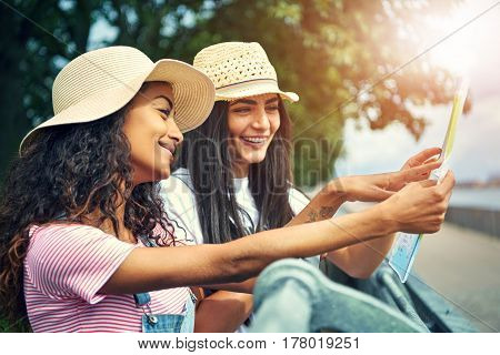 Two Cute Friends In Hats Smiling With Their Map
