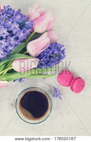 Pink tulips and blue hyacinths fresh flowers with cup of coffee, holiday breakfast, retro toned