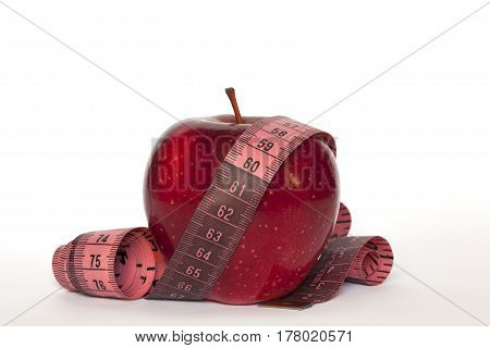 fresh red apple with measuring tape over white background
