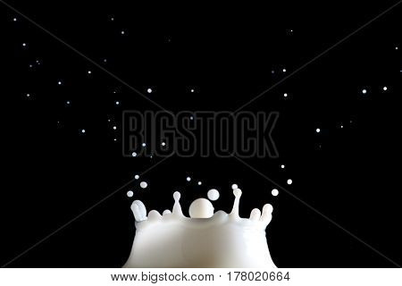 Extreme close-up image of a milk splash with dark background