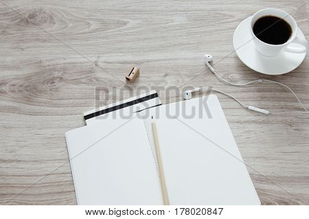 Workplace. On a wooden table there is sketchbooks wooden pencil earphones striped notebook with a white cup of coffee.