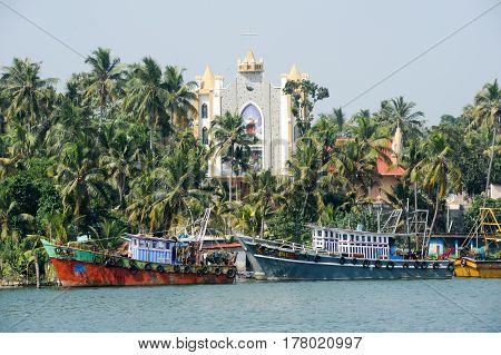 Kollam India - 20 January 2015: fishing boat in front of a church near Kollam on Kerala backwaters India
