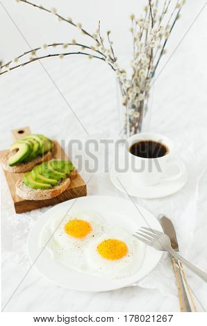 Morning breakfast table setting. On a white plate are two fried eggs on a wooden board sliced avocado a cup of coffee and a vase with a plant. White background daylight vertical image.