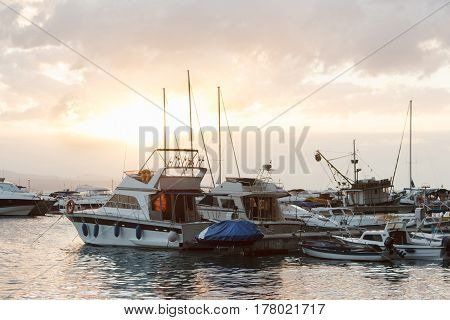 Yachts are moored in the sea against the sunset sky with clouds evening