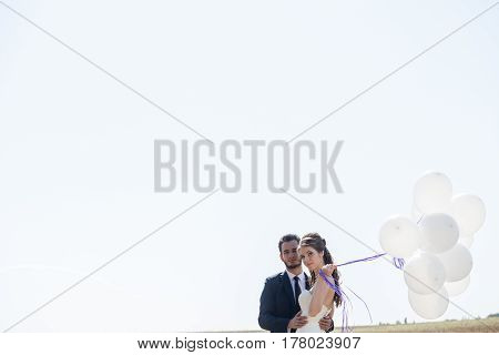 Happy Just Married Couple With Balloons In Hand