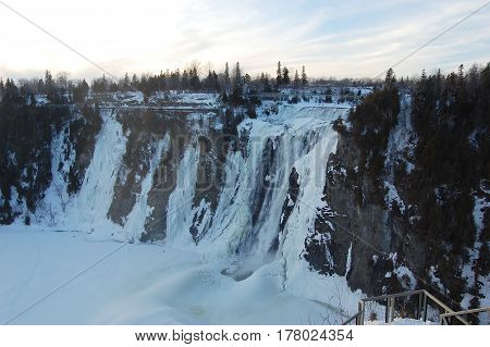 The Montmorency Falls, or Chutes Montmorency in French, is located 7 km east of Quebec City, Canada. The falls is frozen in winter.