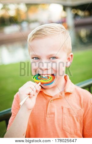 Cute young boy licking a large colorful lollipop outdoors