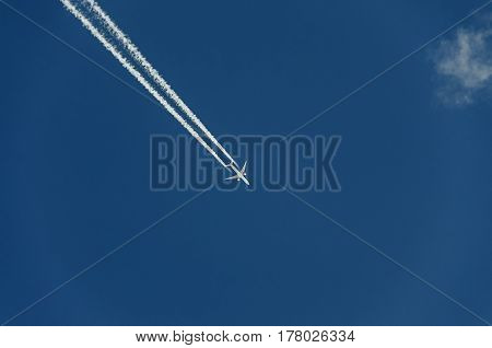 Airplane With Reaction Trail Flying Over Blue Sky With Clouds, Close Up