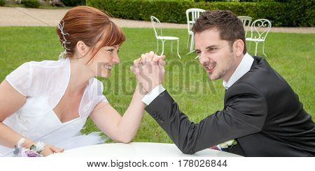 a lovely bride and groom arm wrestling