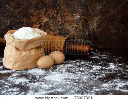 Composition Of Bag Of Wheat Flour, Eggs And Rolling Pin. Preparation For Kneading Dough, Baking On D