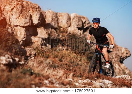 Cyclist in black sportwear Riding the Bike on the Rocky Trail. Extreme Sport Concept. Space for Text. Sportsman in the helmet and sunglasses. Extremal travel in the countryside. Healthy lifestyle. Beautiful landscape.