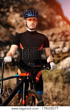 Portrait of male athletic standing with mountain bike in the hill with background of rock. Sportsman in the sportwear, sunglasses and helmet. Travel in the countryside. Healthy lifestyle.