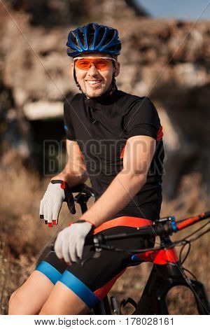 closeup portrait of professional smiling cyclist with his bicycle in the countryside. Background with blurred rock. Sportsman in the black sportwear, helmet and sunglasses. Countryside. Detail. Hands and face.