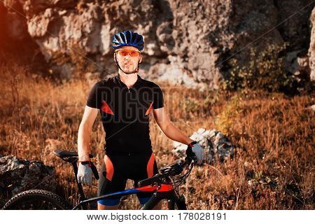 Portrait of a cyclist in helmet and sunglasses on a mountain bike. Active sport in nature. Beautiful landscape. Background. Sportsman in the sportwear. Extremal travel in the countryside. Horizontal photo.