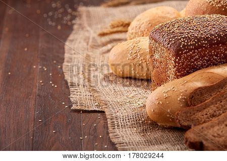 Different bread on burlap on the wooden table close-up. With wheat and ears of wheat. Slices of the brown bread. Rulls and baguette.