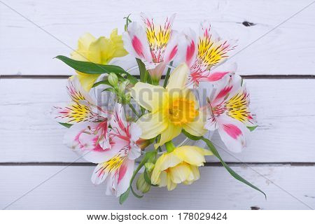 A Bouquet Of Bright Colors: A Daffodil And Alstroemeria In A Vase On A Wooden Table.