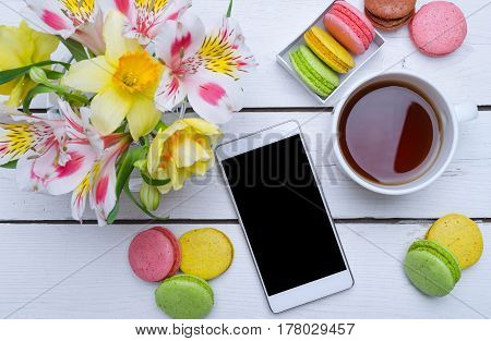 Spring Composition: Bright Colors, Multicolored Macaroons And Cup Of Tea On A Wooden Table.