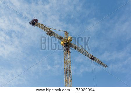 Yellow construction crane on blue sky background. Sunny day horizontal image.